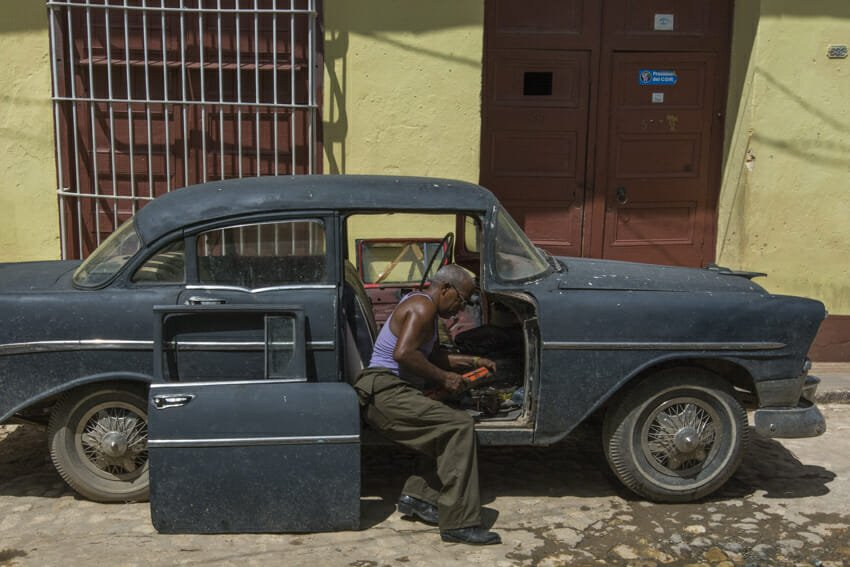 Patching an old american car, Trinidad - people